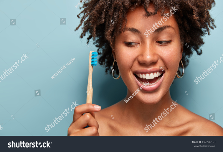 Woman prepares to clean her teeth with a toothbrush